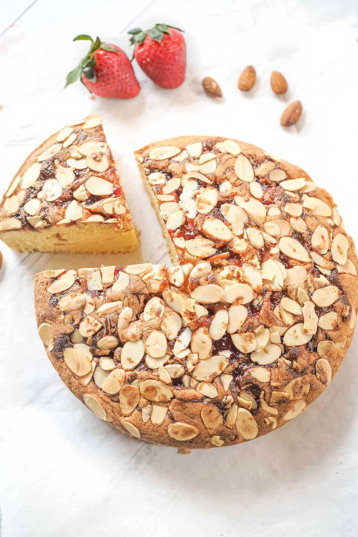 A round cake with strawberry filling and almond flakes topping. A slice of the cake is cut out