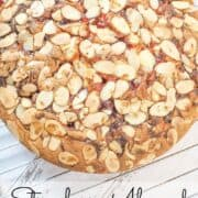 A round cake with strawberry and almond flakes topping