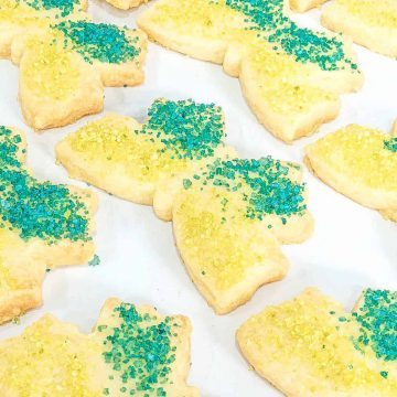 Top view of butterfly shaped cookies decorated in blue and green sanding sugar