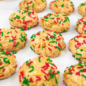 A group of cornflake cookies decorated with red, green and gold sprinkles