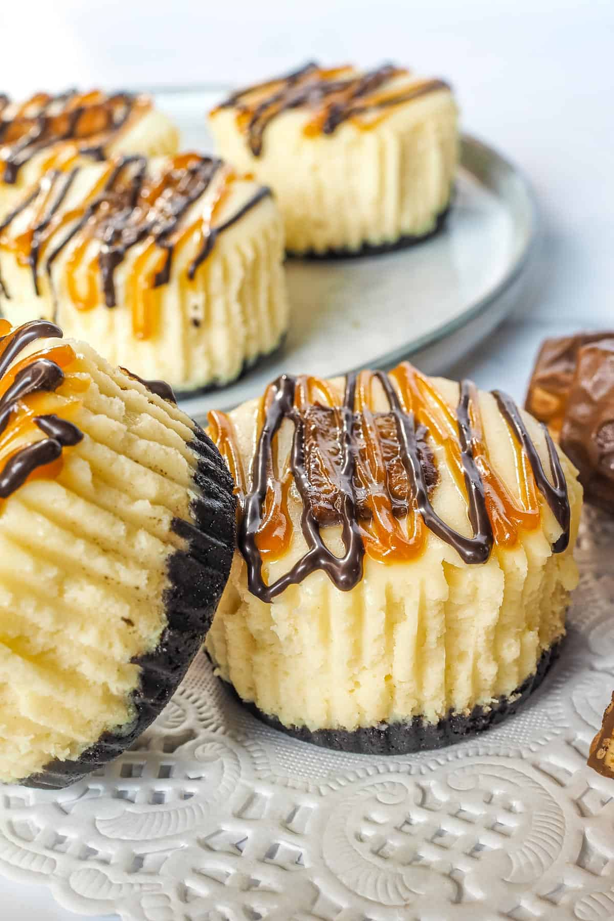 Mini cheesecakes decorated with Snickers chocolate and chocolate and caramel drizzles on a grey plate