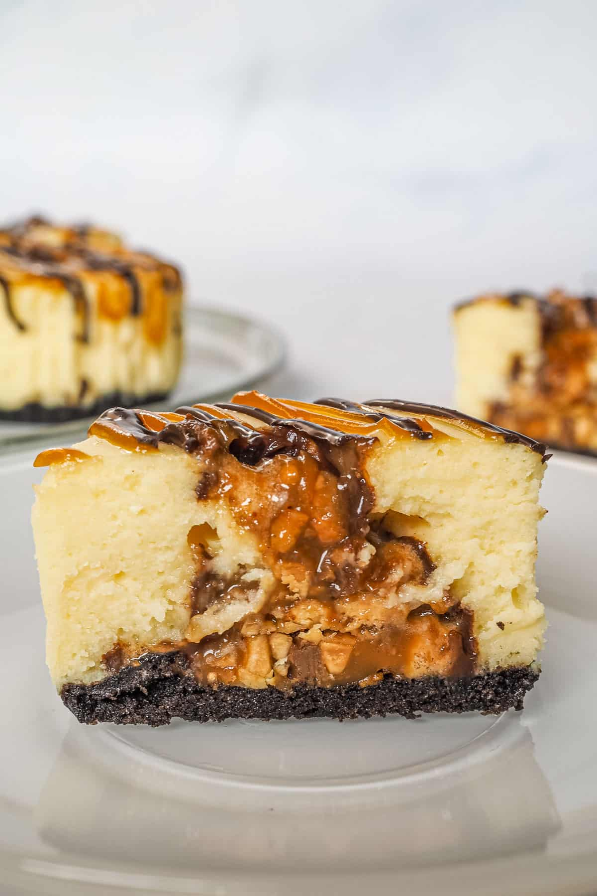 A mini cheesecake cut into half, showing the Snickers candy filling