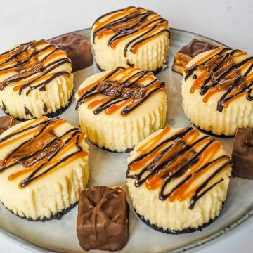 6 mini cheesecakes decorated with Snickers chocolate and chocolate and caramel drizzles on a grey plate