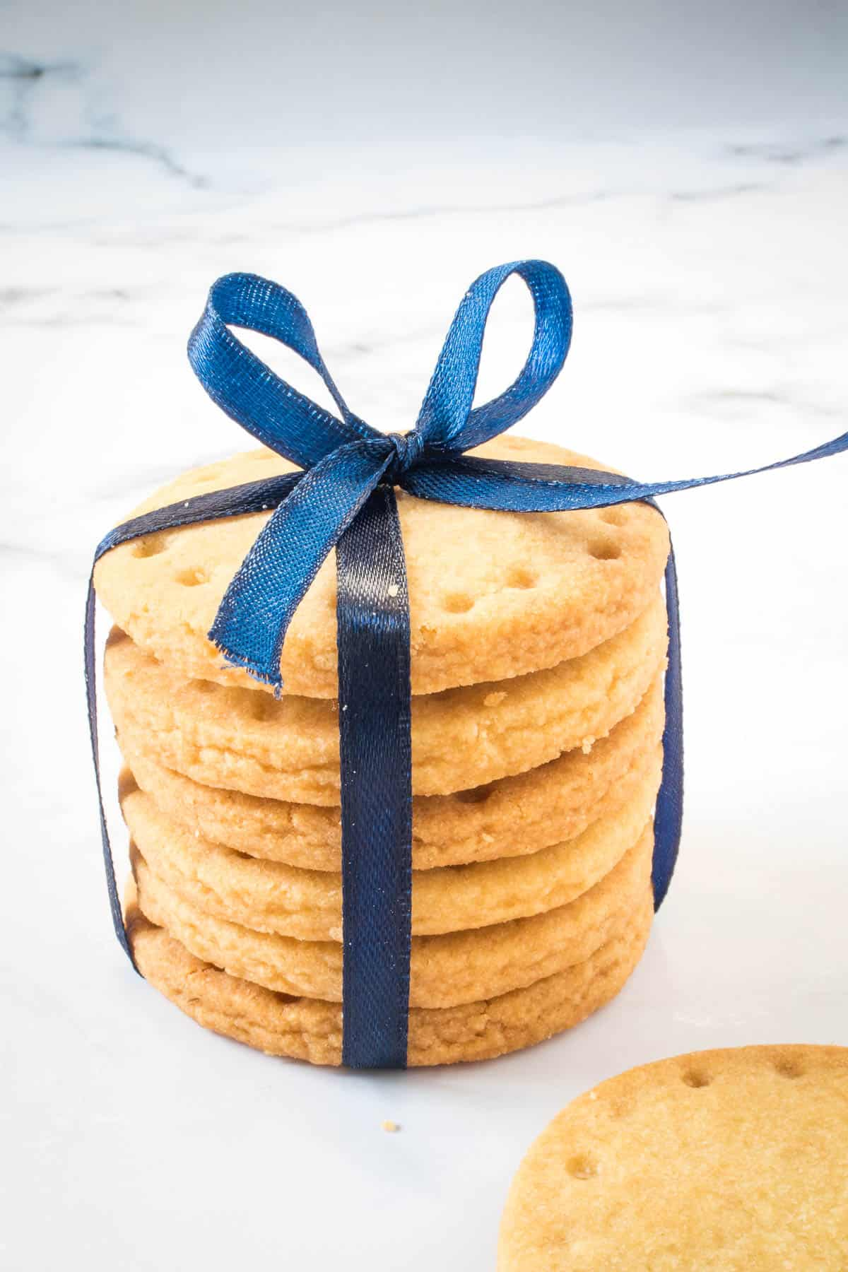 A stack of round cookies tied in blue ribbon