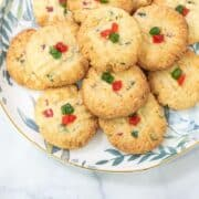 Round cookies with red and green glace cherry cubes decoration, on a leaf motif plate