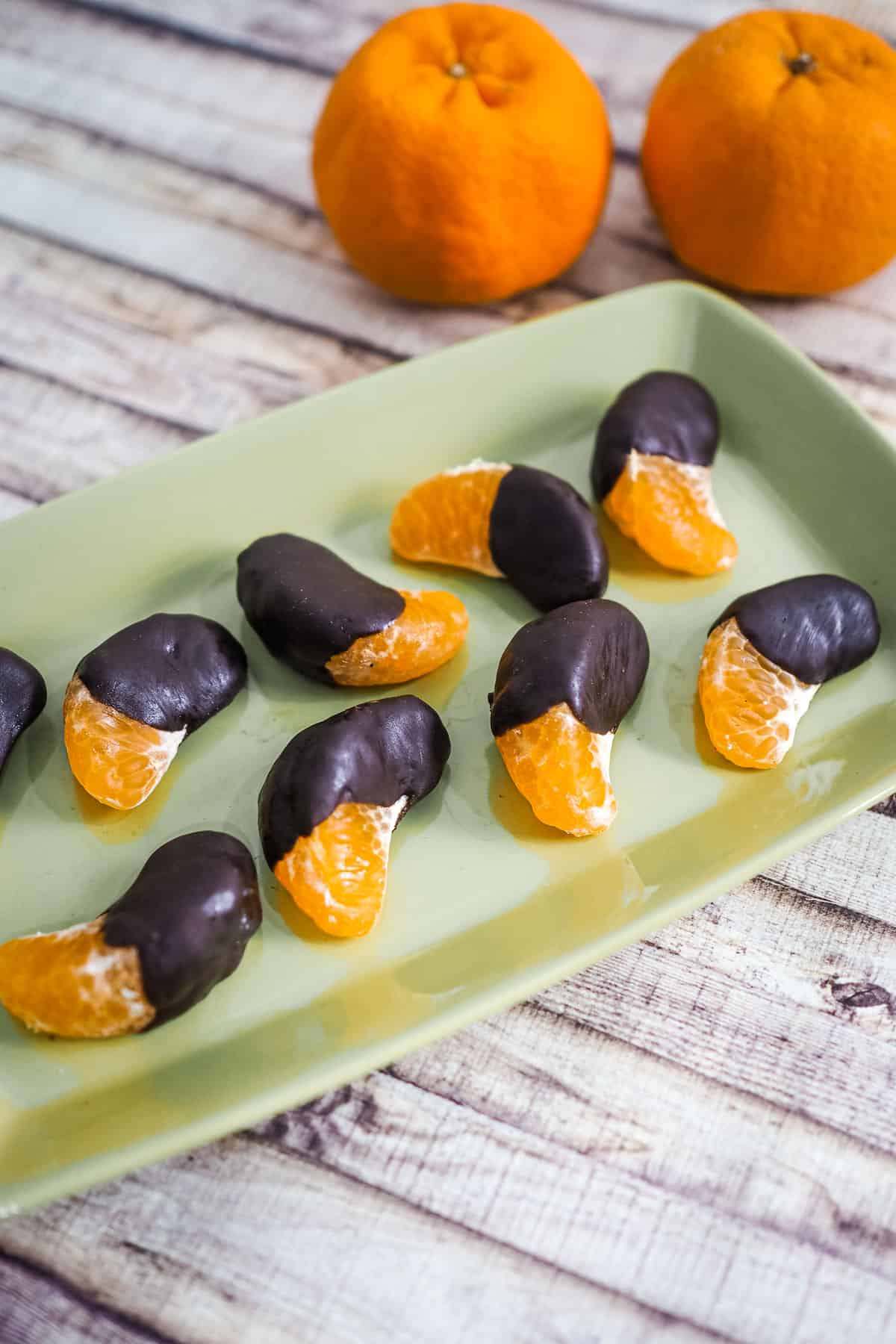 Chocolate dipped orange segments on a green rectangle plate against a white wood background