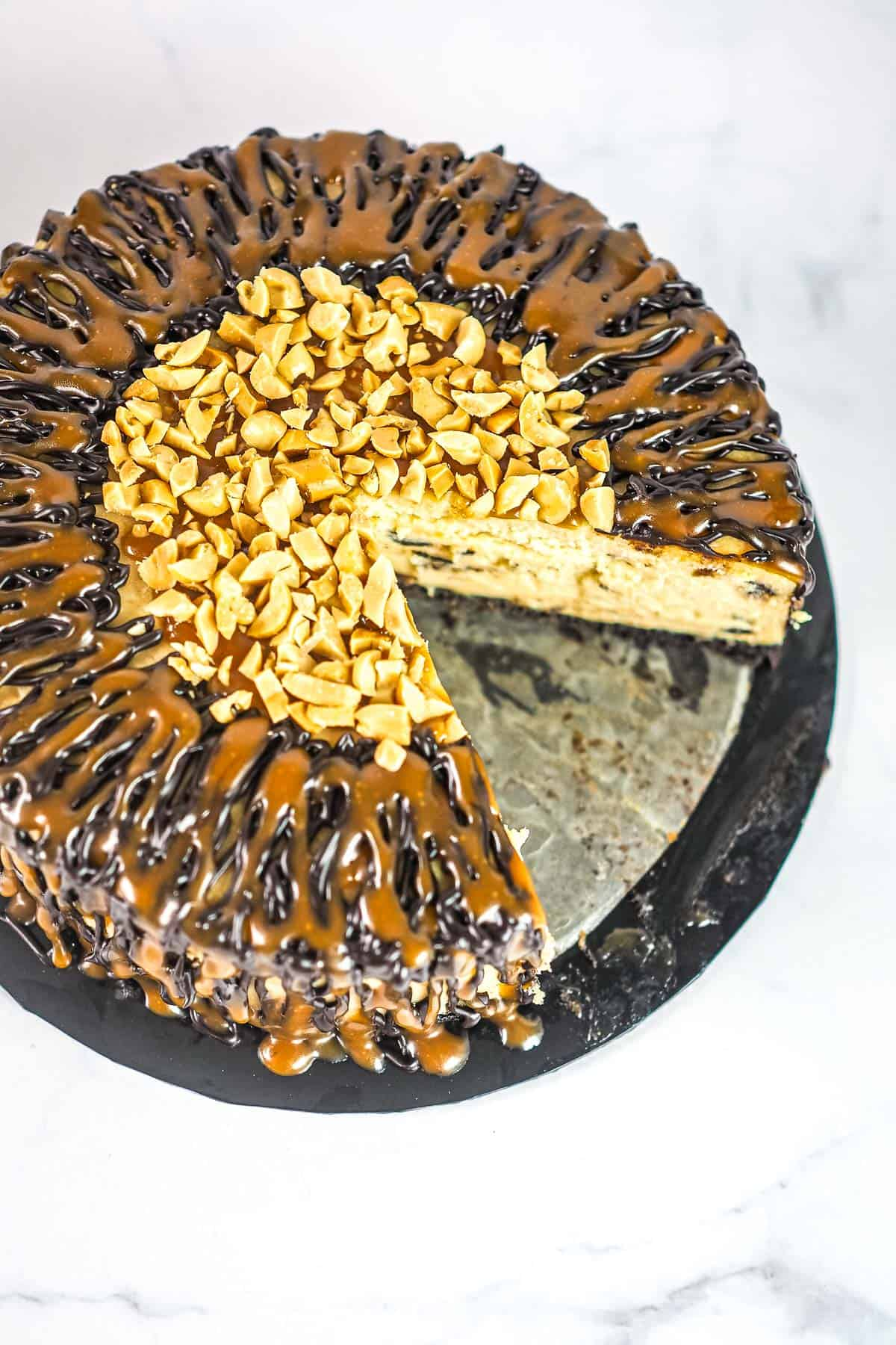 A round chocolate peanut butter cheesecake with caramel and chocolate drizzle and chopped peanut center. A slice of the cake is cut out