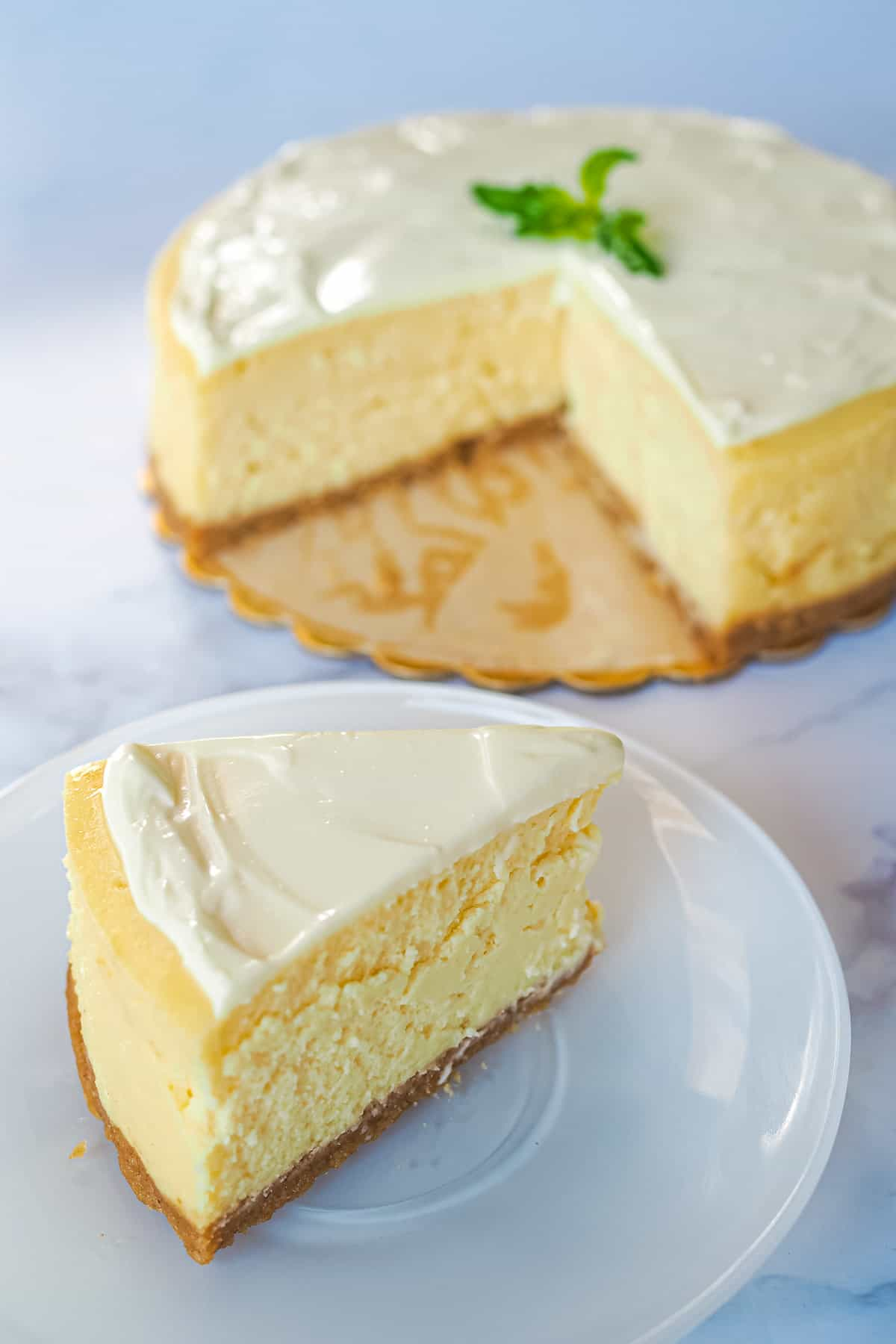 A slice of New York cheesecake with sour cream topping