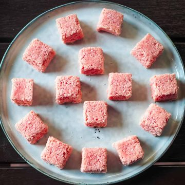 Blocks of coconut candy in pink on a white plate