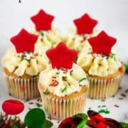 5 cupcakes decorated with red star toppers and Christmas themed sprinkles