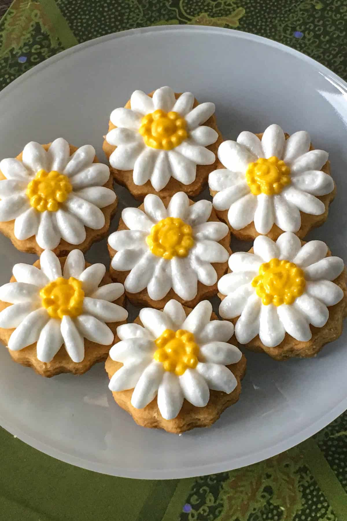 Sugar cookies decorated with royal icing piped daisies