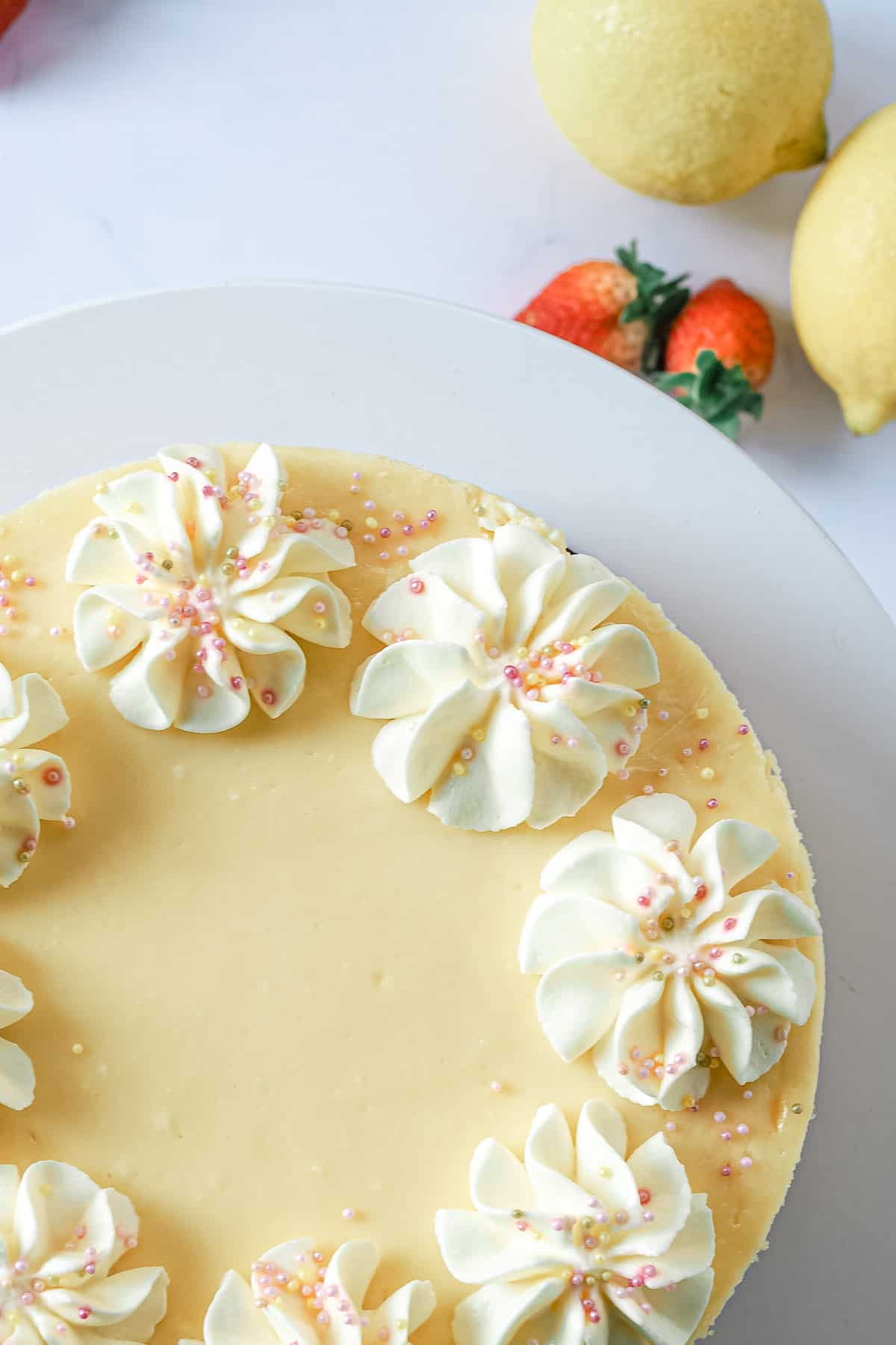 Close up of a round cheesecake with piped cream topping and sprinkles