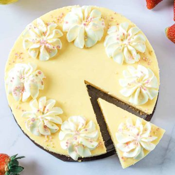 A round cheesecake decorated with cream swirls and sprinkles with a slice cut out