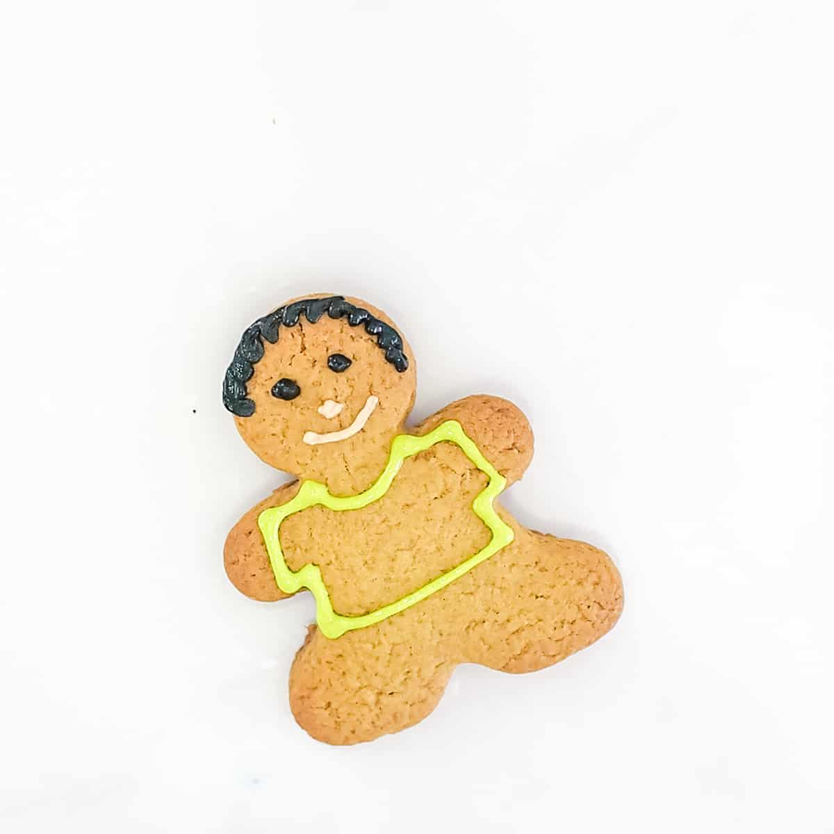 A gingerbread boy cookie with a green icing outline for the shirt