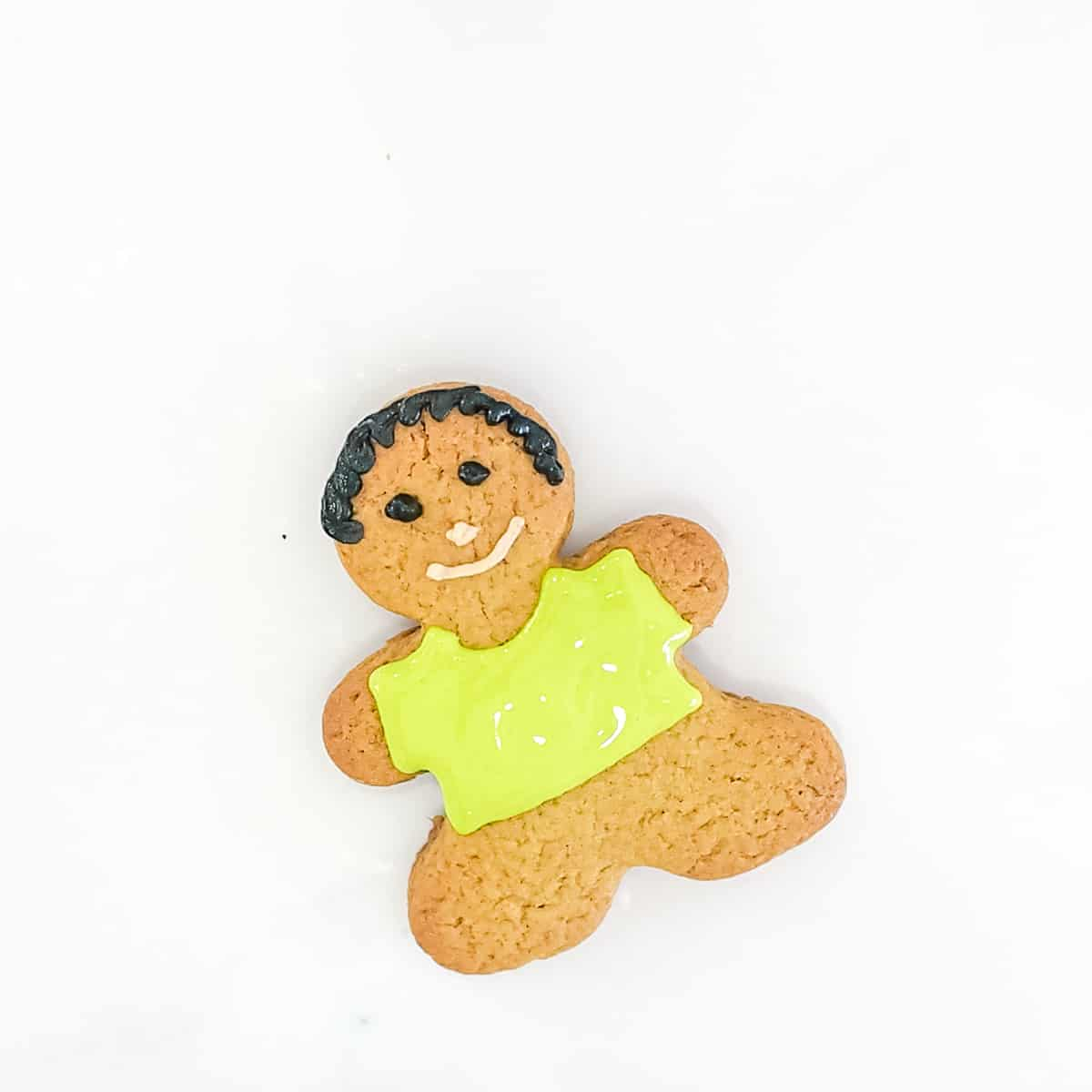 A gingerbread cookies decorated as a boy with green shirt.