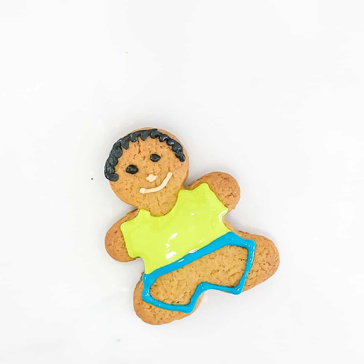 A gingerbread cookie decorated as a boy with green shirt and blue outline for pants