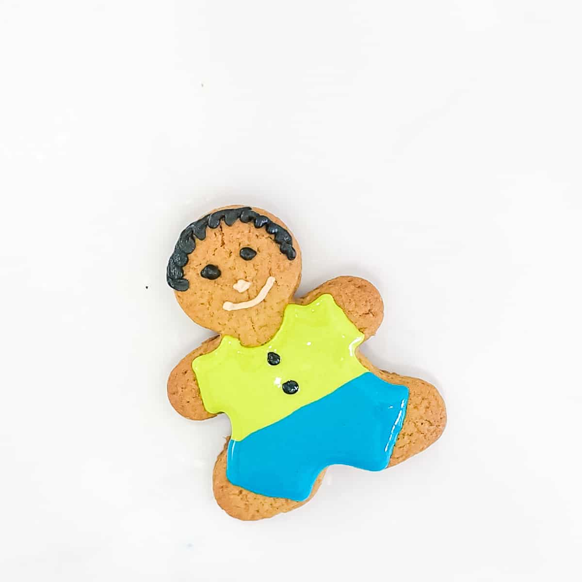 A gingerbread boy cookie with green icing shirt and blue icing pants.