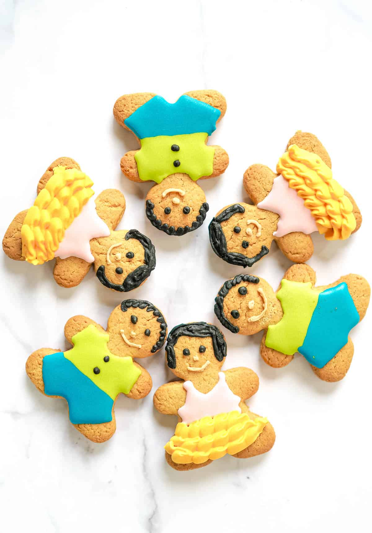 Gingerbread cookies decorated into boys and girls. A total of 6 cookies arranged into a circle