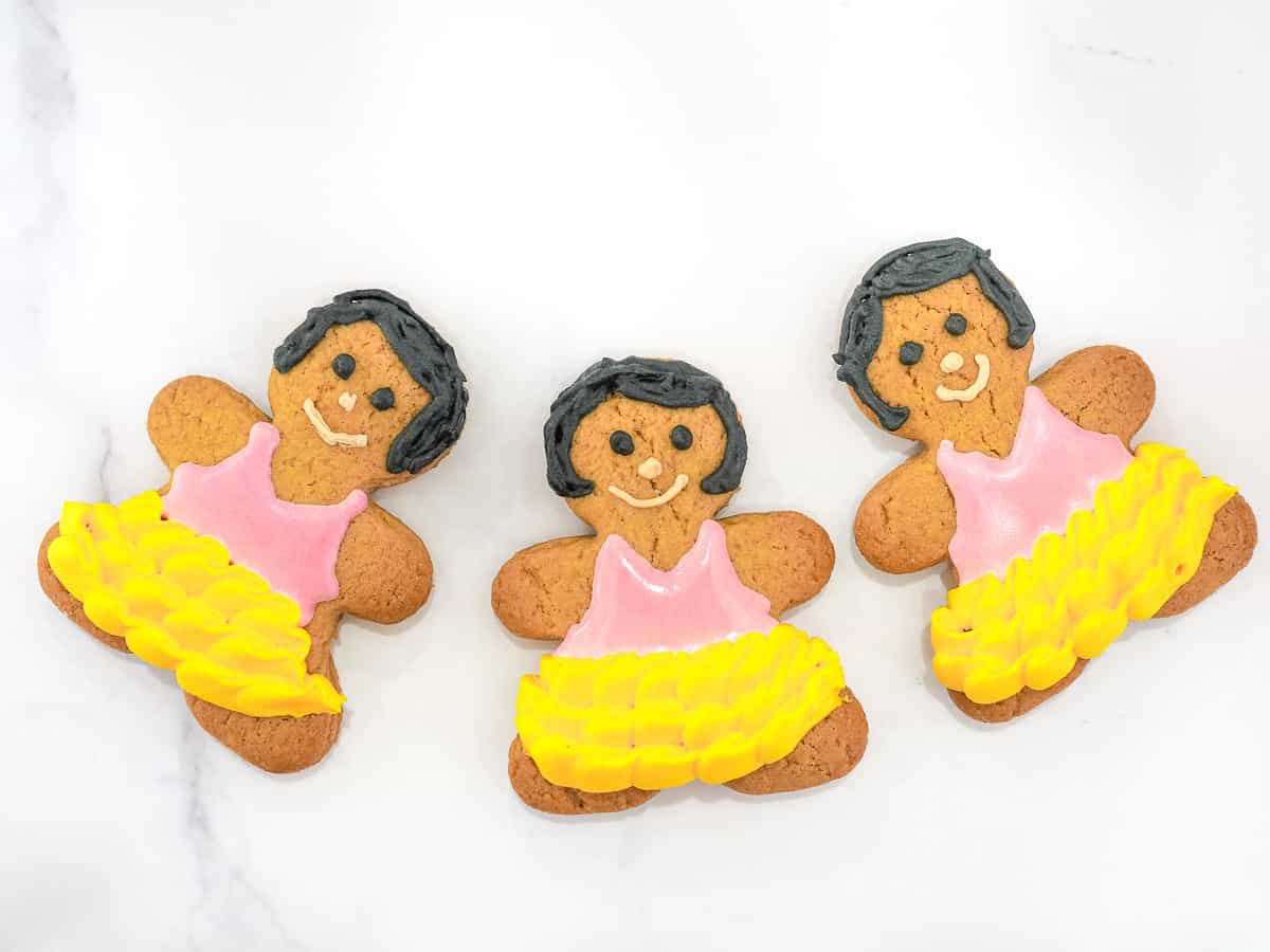 3 gingerbread girl cookies with pink icing blouse and yellow icing frilly skirt.