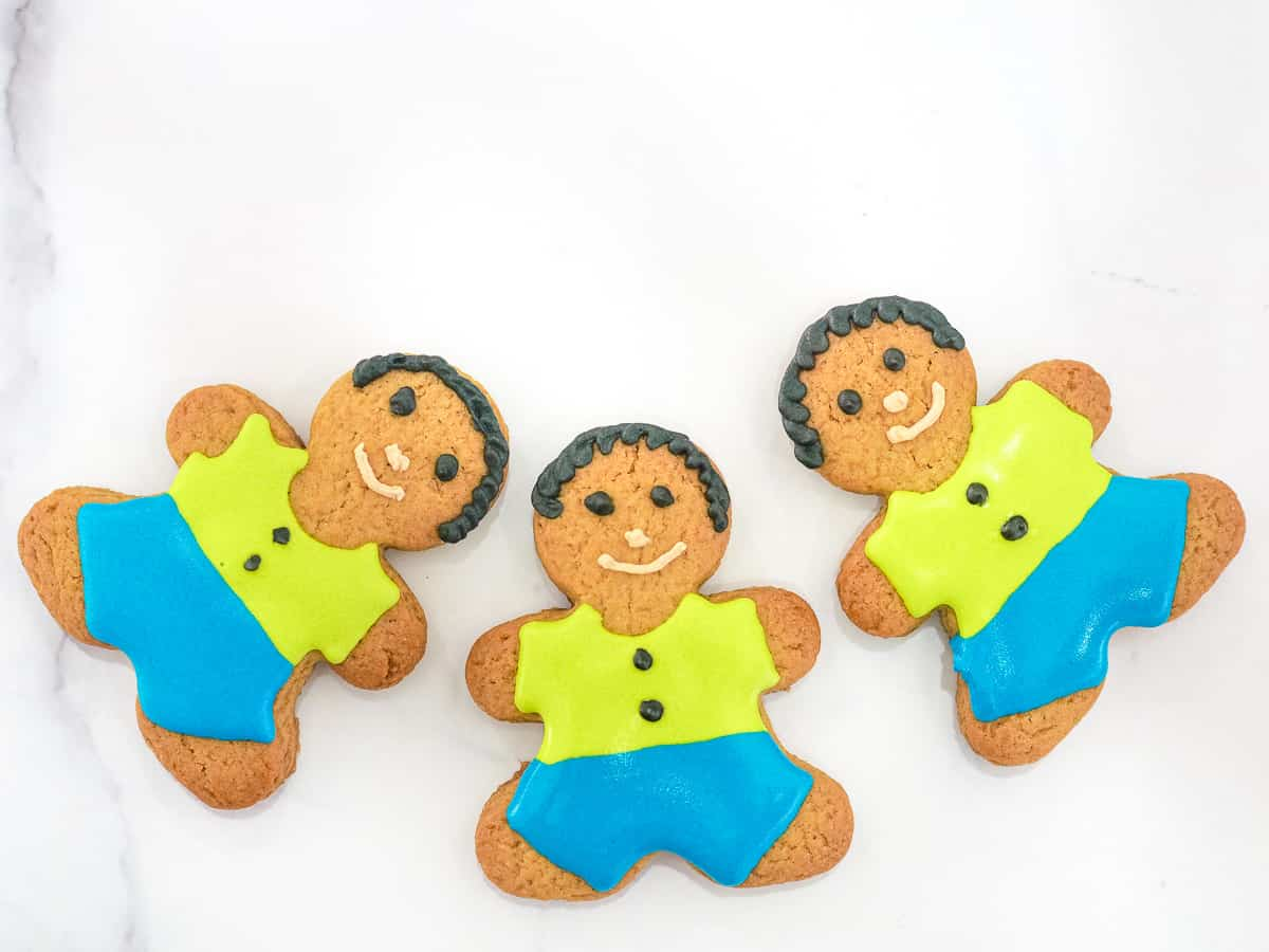 3 gingerbread boy cookies with green icing shirt and blue icing pants.