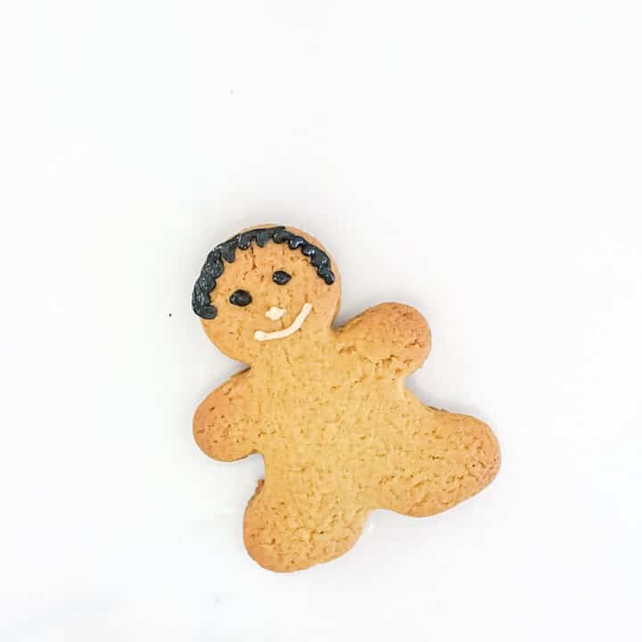 A gingerbread cookie decorated with black hair, black eyes and peach nose and mouth.