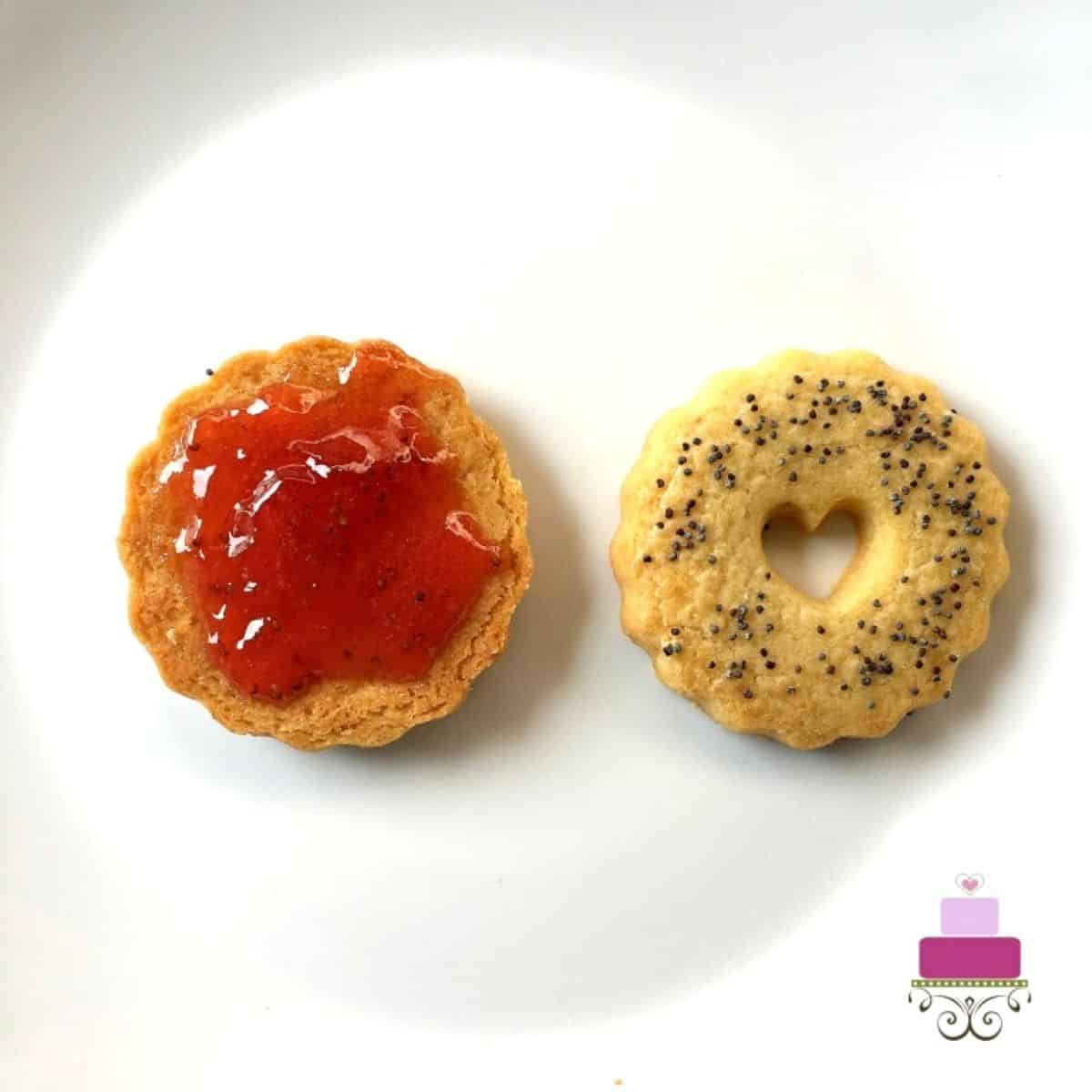 A round cookie with jam on top. At the side is a round cookie with heart shaped hole in the center.