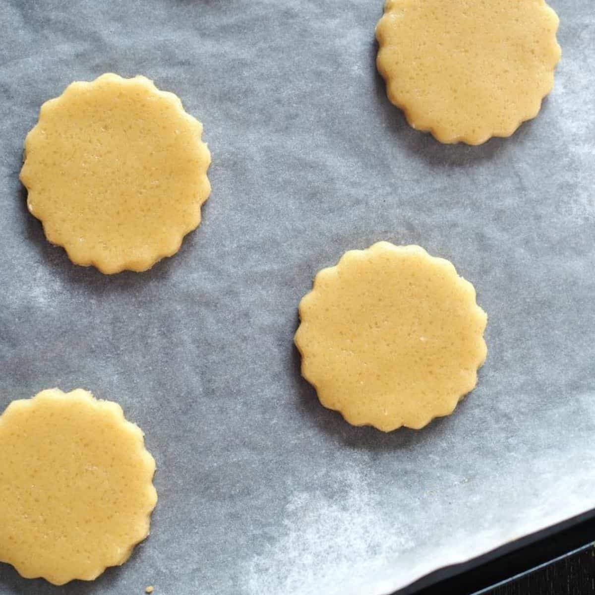 Round scalloped cookies on a parchment lined tray
