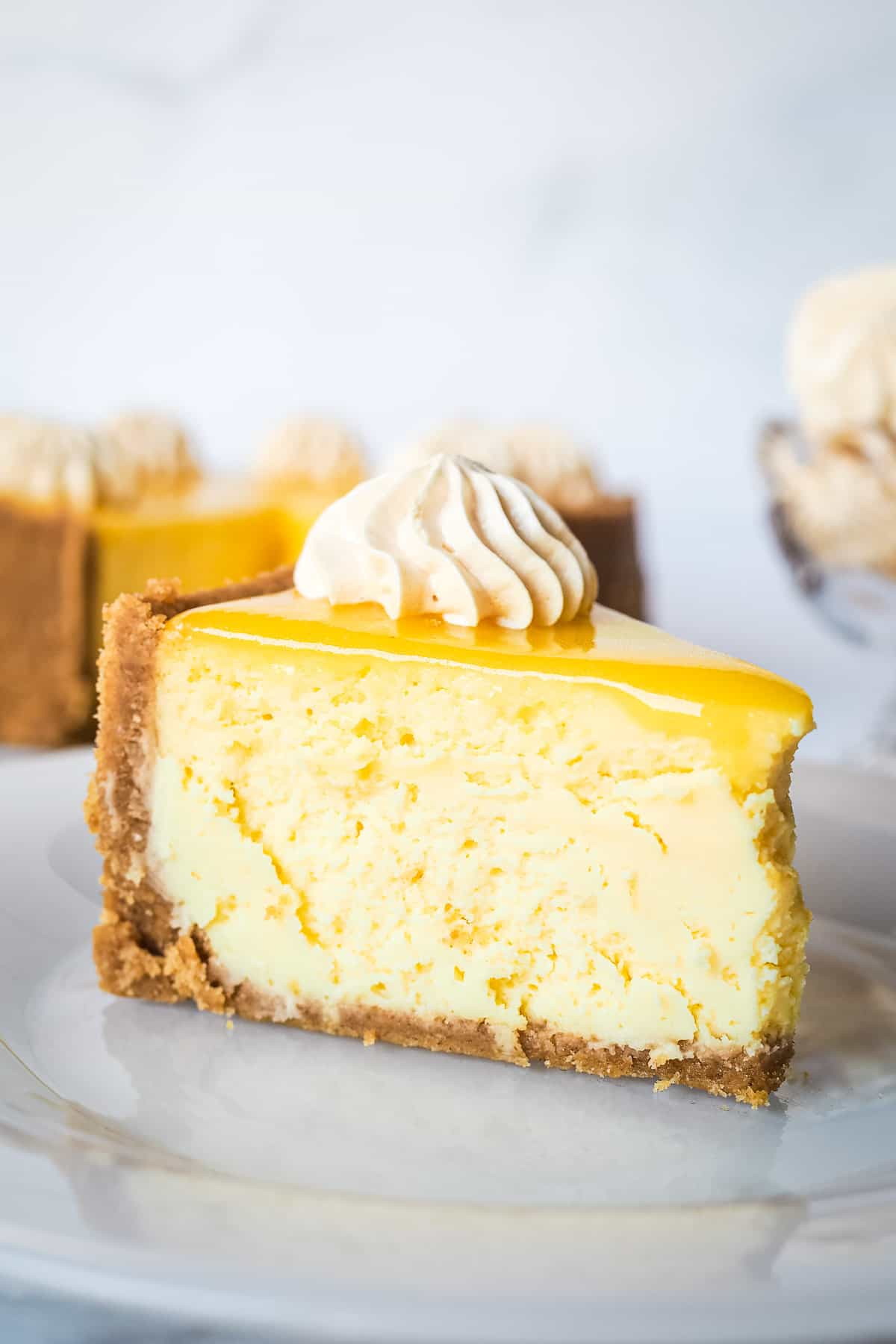 A slice of lemon curd cheesecake on a white platee