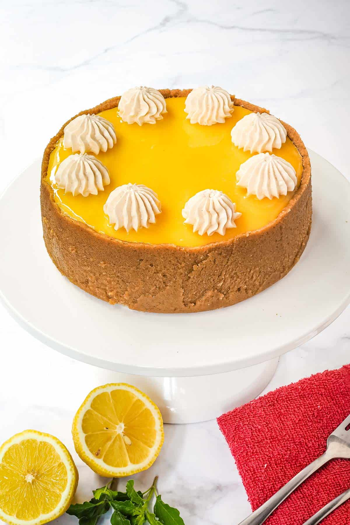 A round cheesecake with high crust, lemon curd topping and meringue cookies decoration