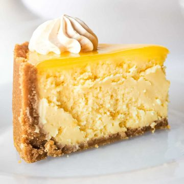 A slice of lemon curd cheesecake on a white plate