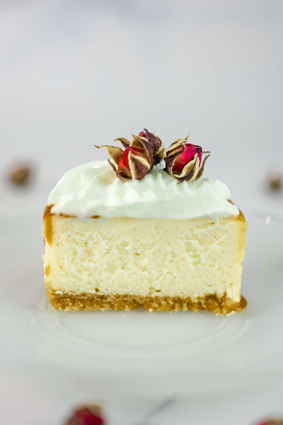 A small round cheesecake cut into half. Cake is topped with cream and dried rose buds