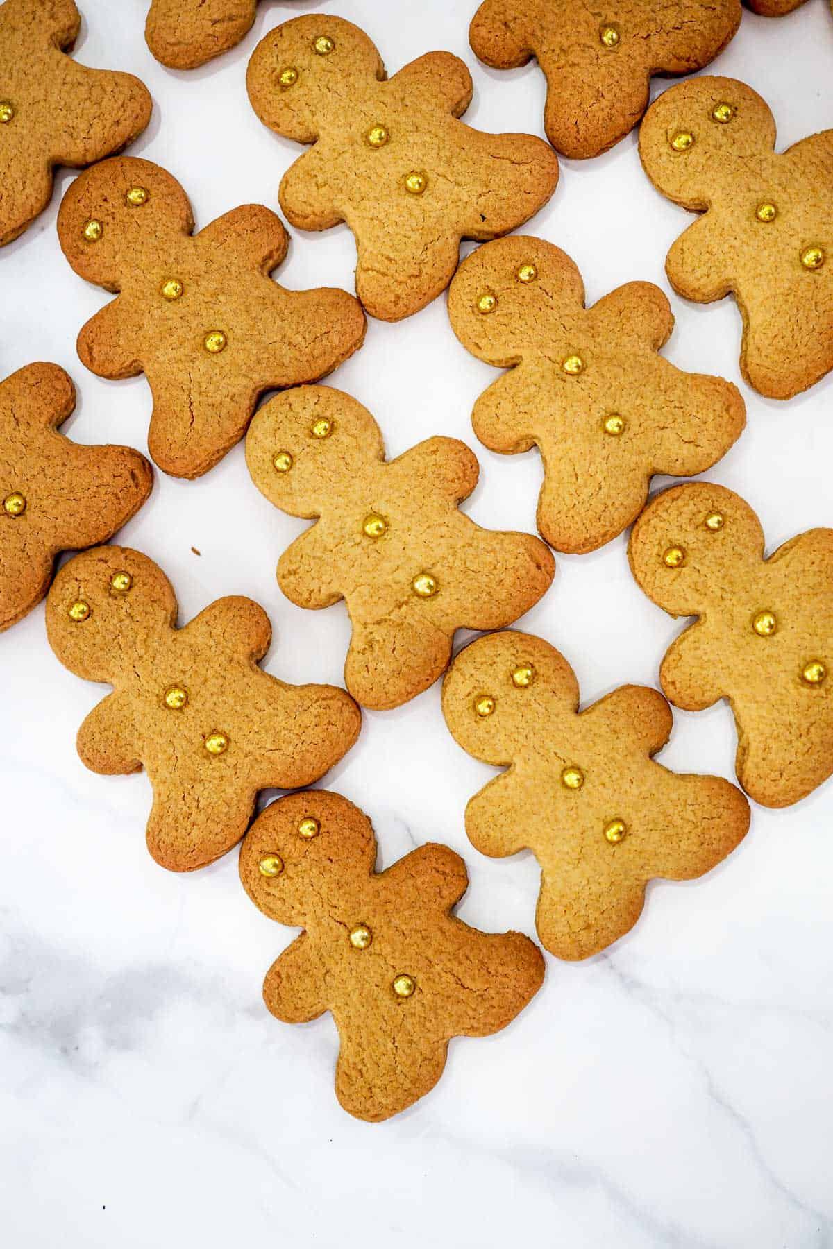 Gingerbread cookies cut into gingerbread men shapes and decorated with gold dragees
