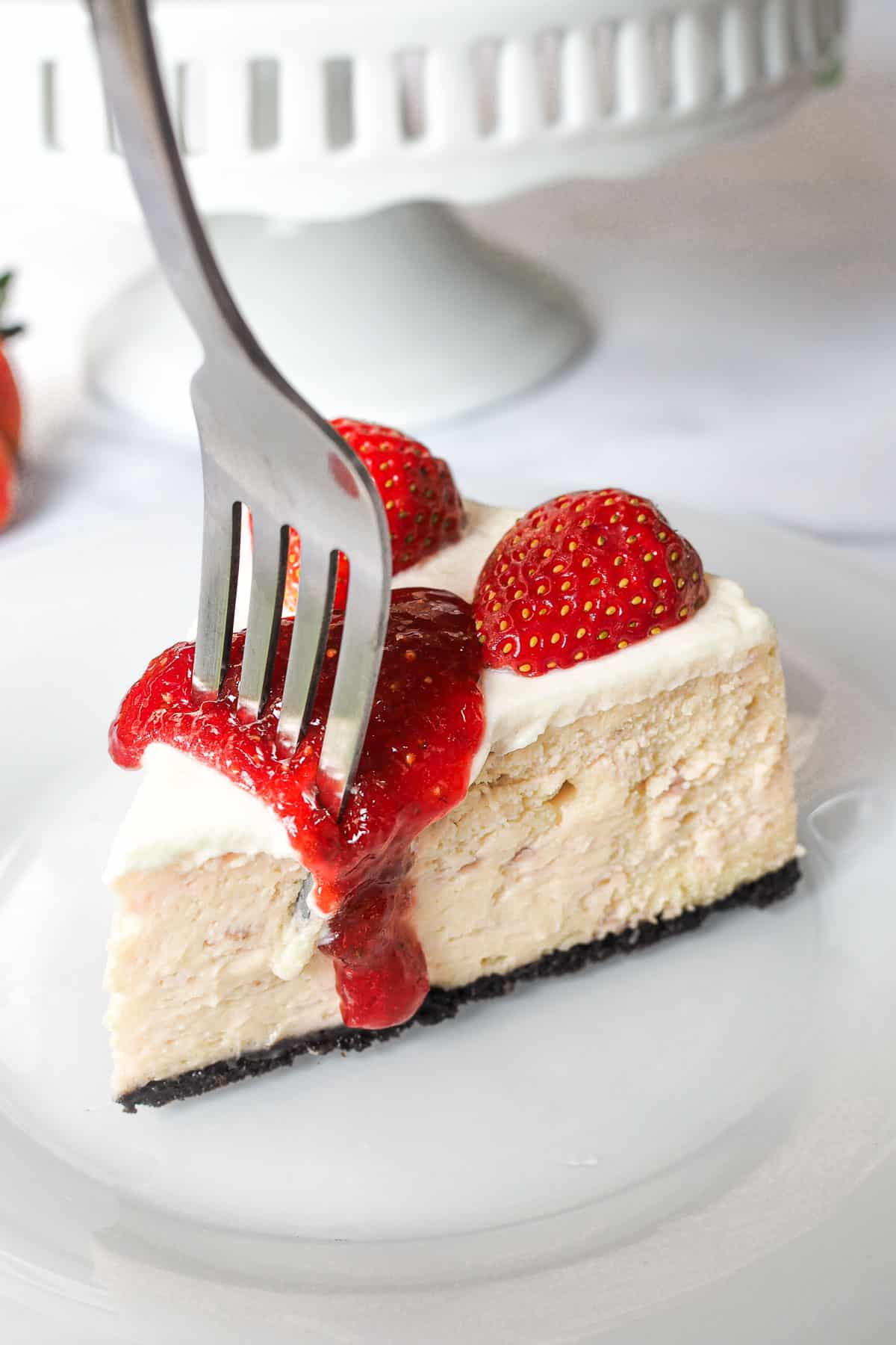 Digging into a slice of a Oreo strawberry cheesecake slice with a fork