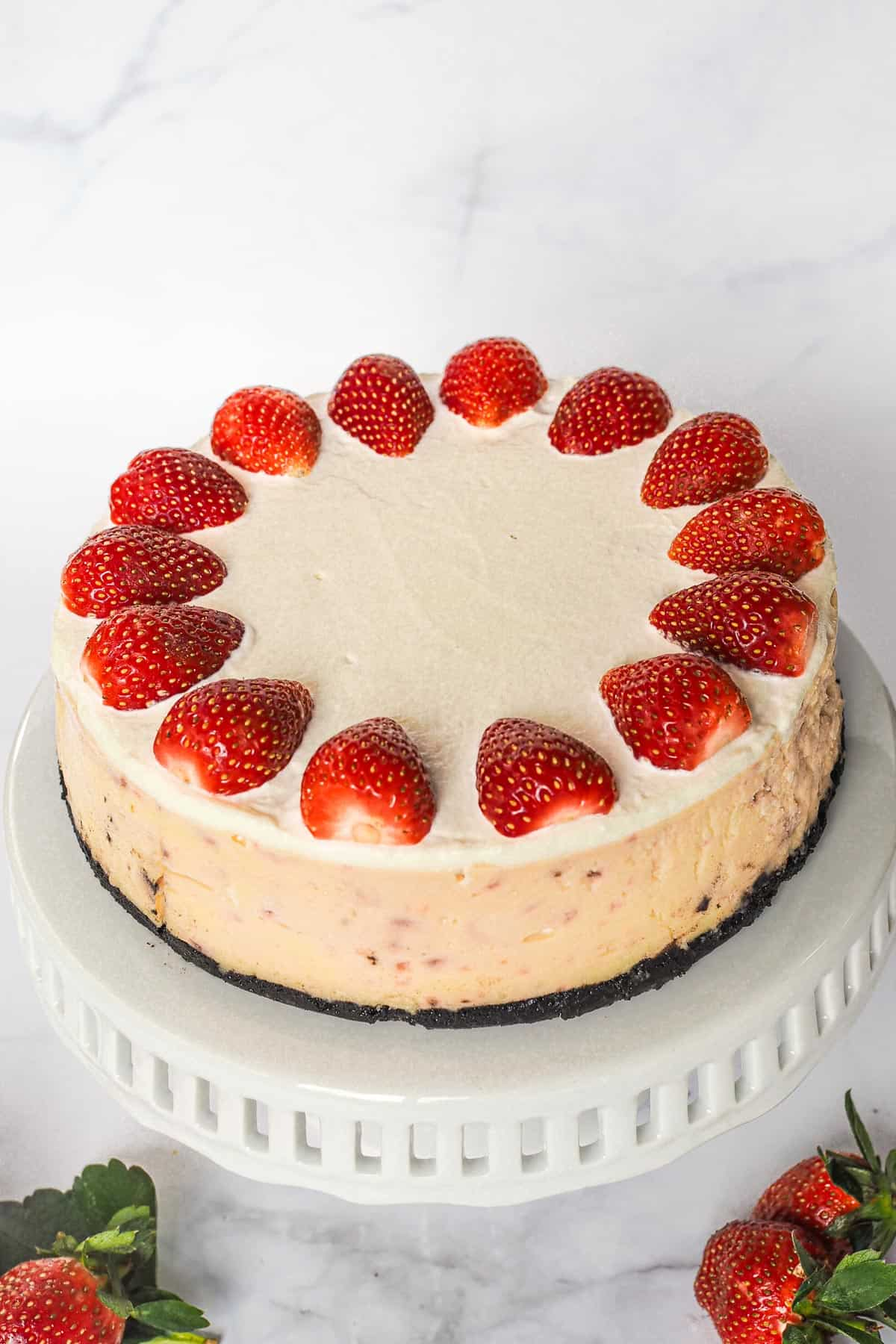 A round cheesecake with Oreo crust and fresh strawberries