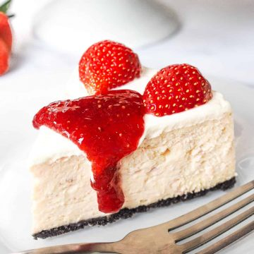 A slice of Oreo strawberry cheesecake with strawberry topping and fresh strawberries