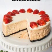 A round strawberry cheesecake with a slice cut out