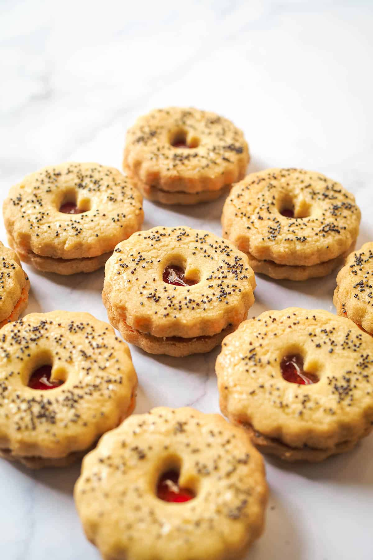 Round scalloped cookies sandwiched with strawberry jam. Cookies are with a small heart shaped hole on top