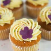 A set of cupcakes in white cupcake casings decorated with buttercream, sugar sprinkles and a pretty 5 petal fondant flower