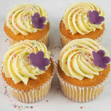 A set of 4 cupcakes in white cupcake casings decorated with buttercream, sugar sprinkles and a pretty 5 petal fondant flower