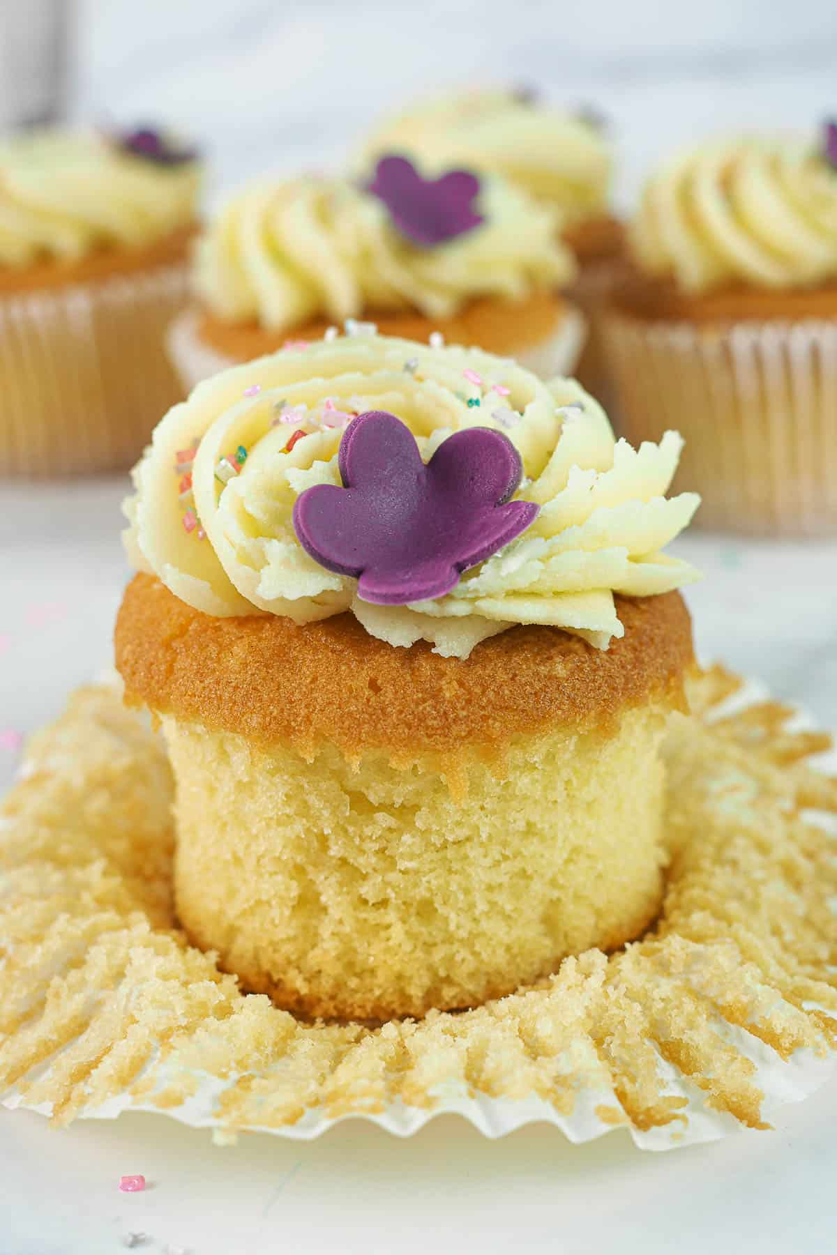 A cupcake with its casing peeled open. Cupcake is decorated with a simple buttercream swirl, sugar sprinkles and a purple 5 petal fondant flower