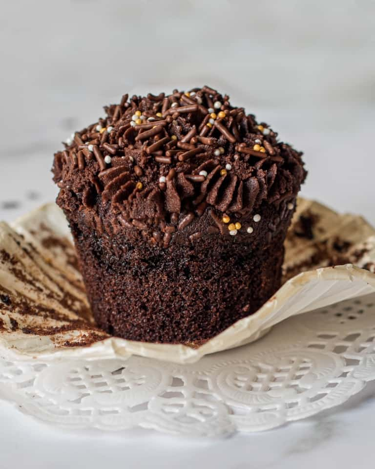 Chocolate cupcake with chocolate buttercream in white cupcake casings. Cupcakes are topped with gold and chocolate sprinkles