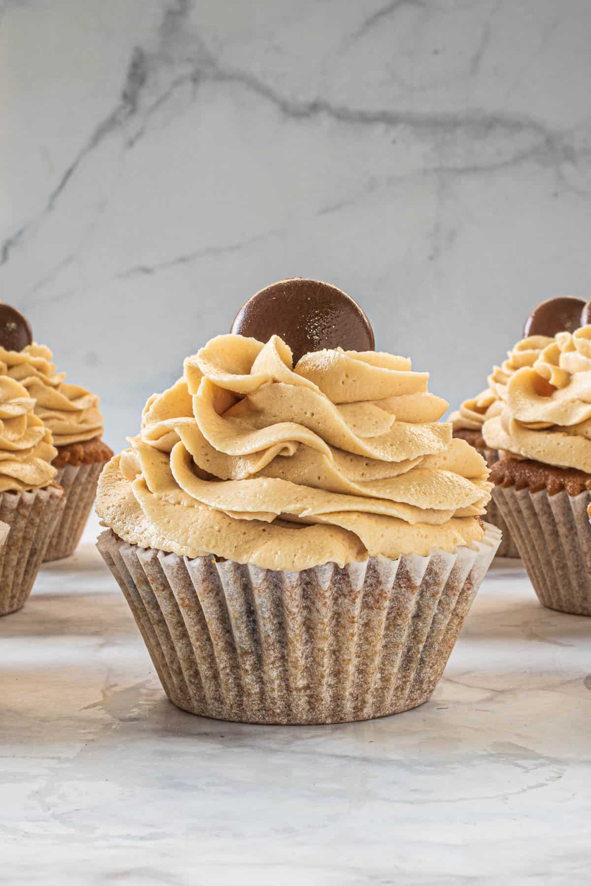 Coffee cupcakes in white cupcake casings, decorated with buttercream swirl and chocolate coin