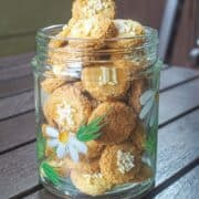 A jar of cookies decorated with white sprinkles
