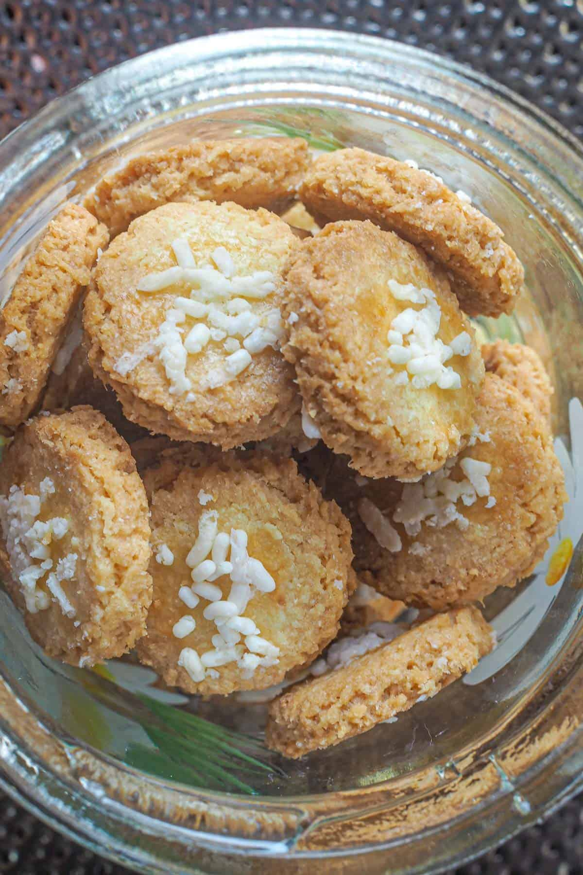 Close up of crispy coconut cookies with white sprinkles topping in a jar
