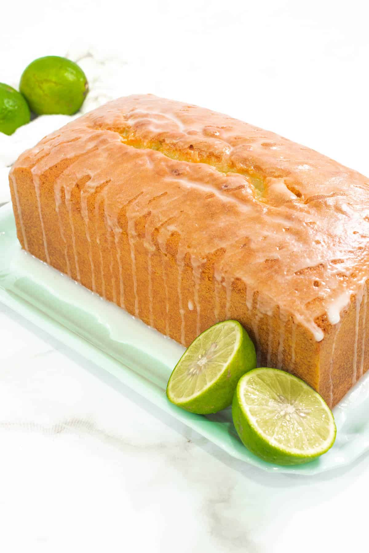 Lime pound cake loaf on a green tray with limes on the side