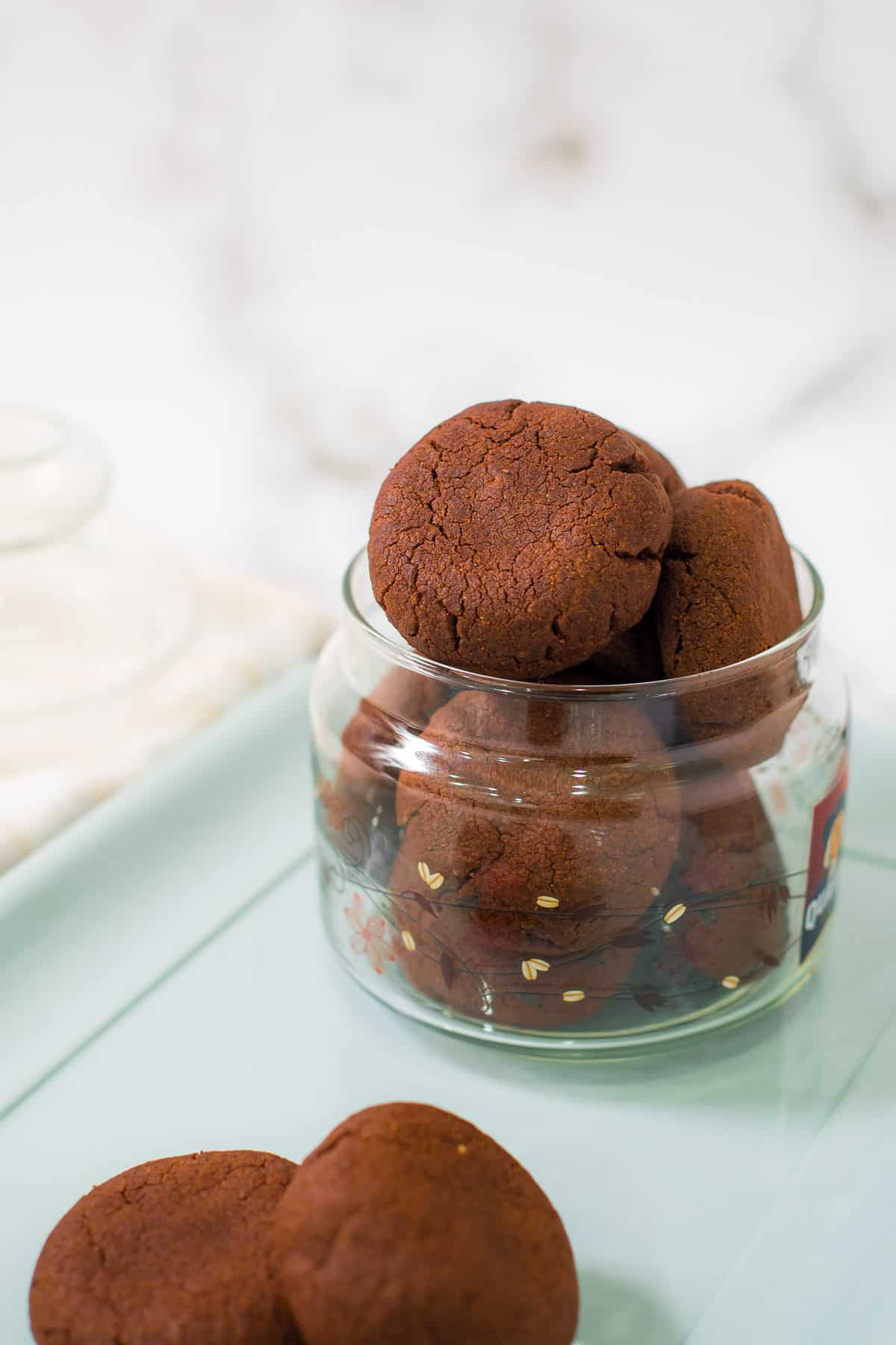 A glass jar of round chocolate cookies
