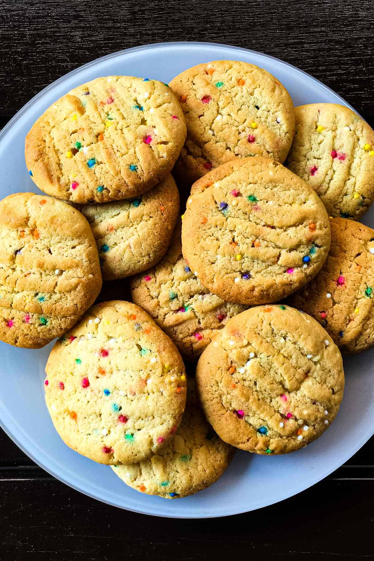 Round cookies with sprinkles on a white plate