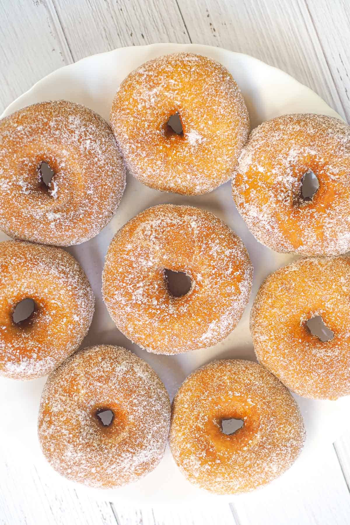 Ring donuts coated in sugar on a plate