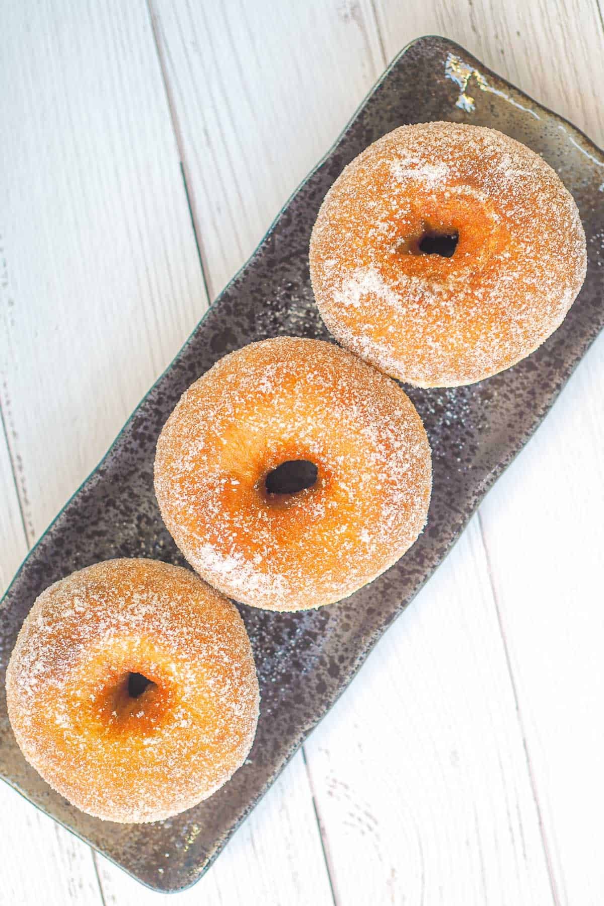 3 brioche donuts on a brown rectangle plate