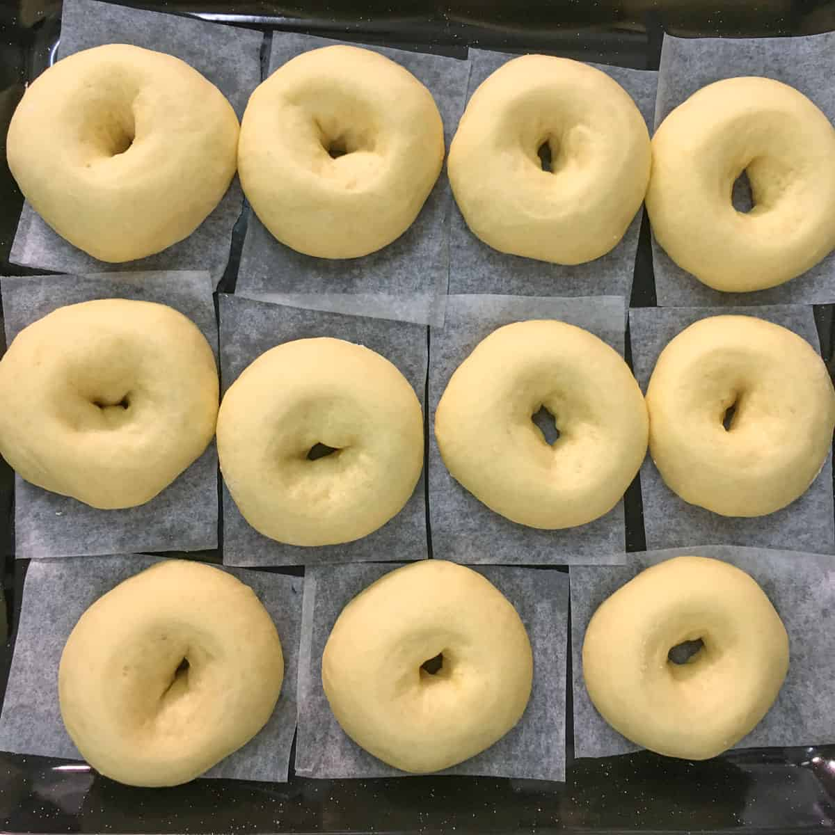 Proofed donuts on a black tray